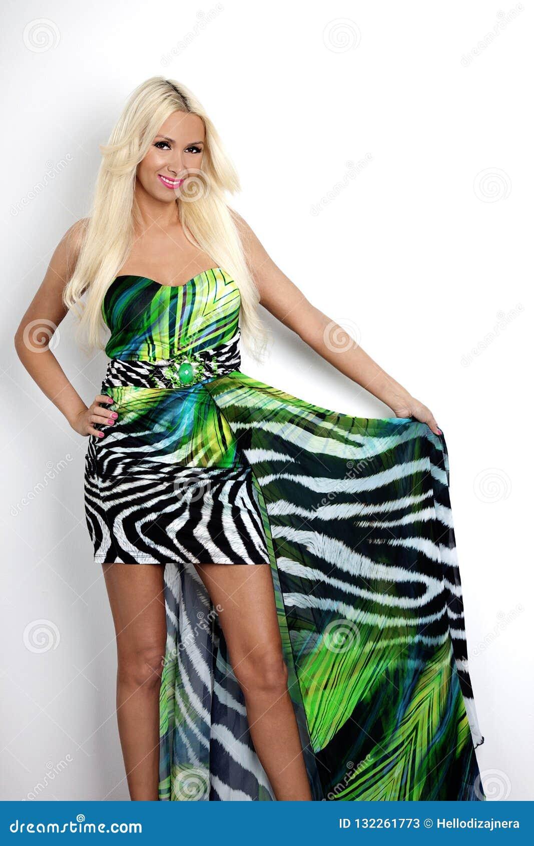 O bonito, feliz Mulher de sorriso loura O tiro da forma e da beleza Modelo que veste o vestido colorido elegante