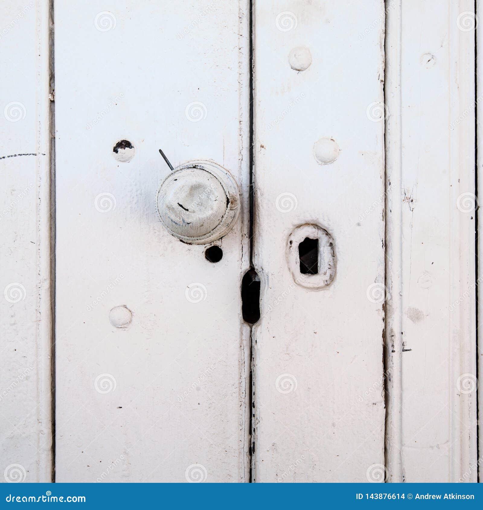 O botão de porta amolgado em um velho pintou a porta de madeira