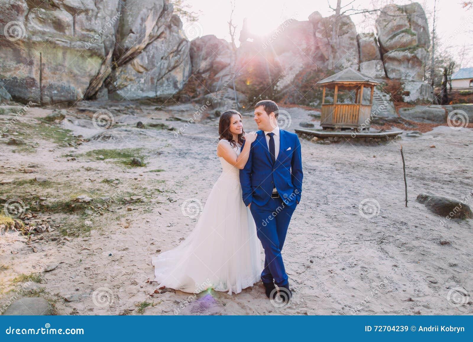 O branco feliz novo vestiu a noiva que inclina-se no ombro de seu noivo seguro considerável no terno azul