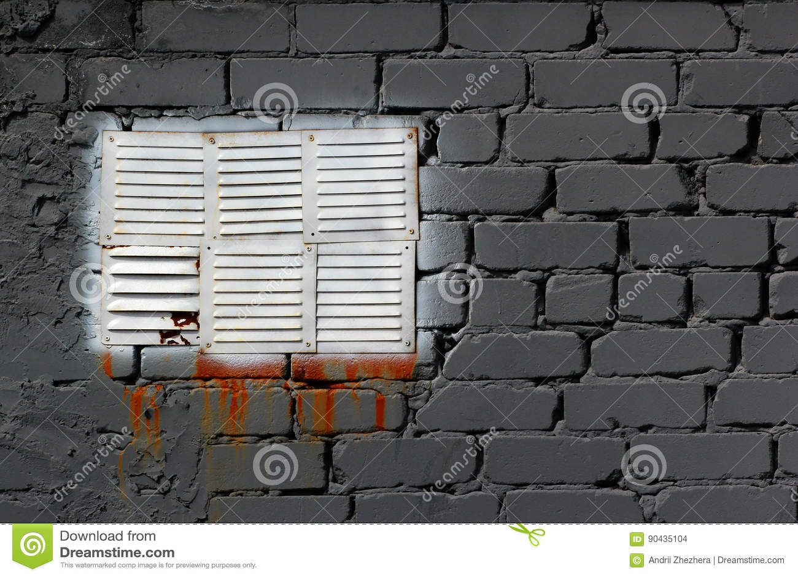 O branco pintou a janela do respiradouro do metal na parede de tijolo cinzenta