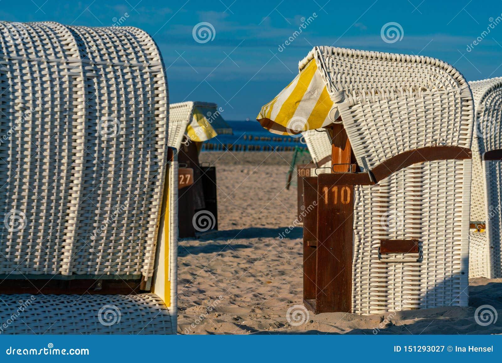O branco telhou cadeiras de praia de vime na luz solar dourada