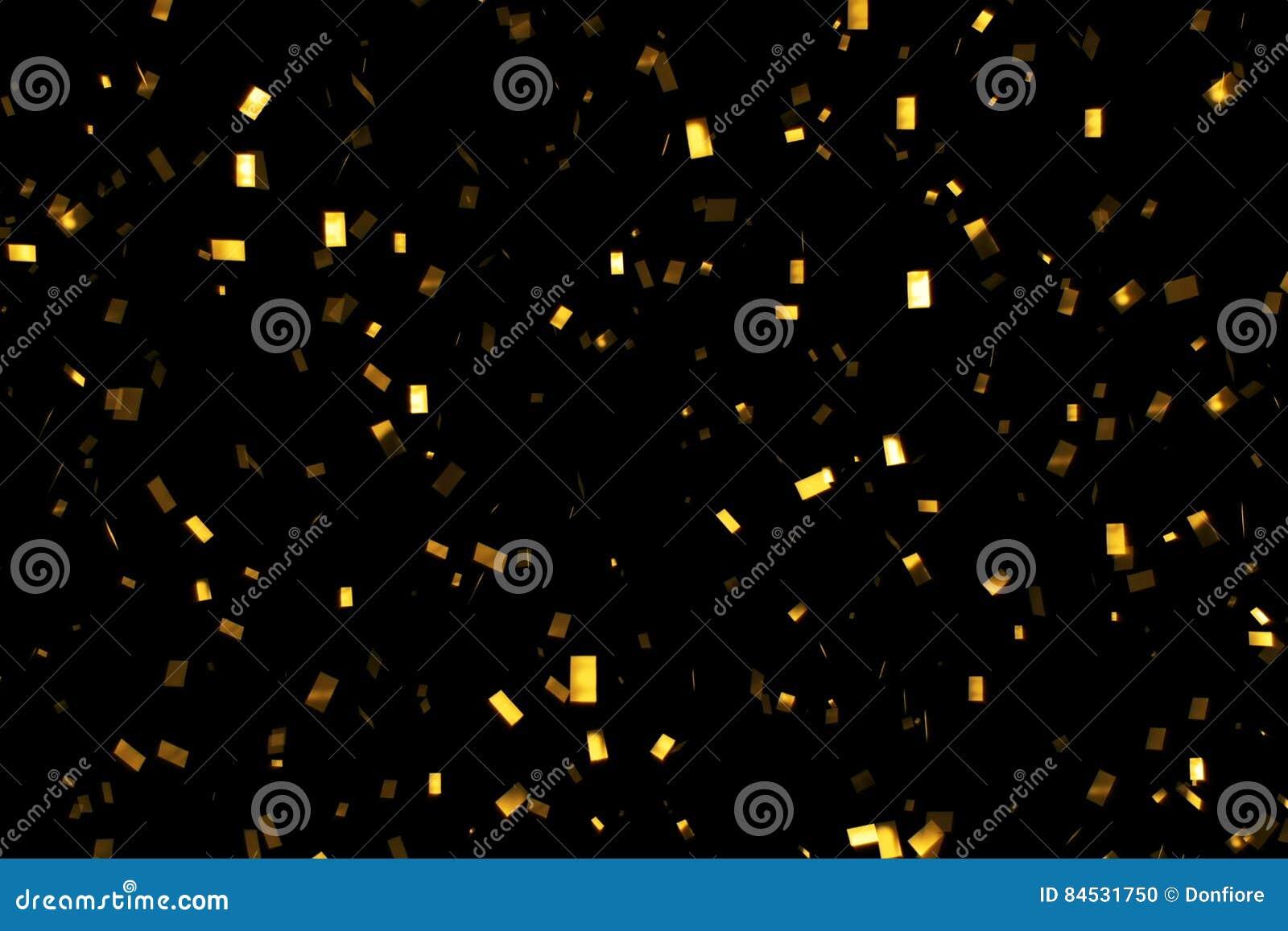 O brilho de queda do ouro foil confetes, no fundo preto, no feriado e no divertimento festivo