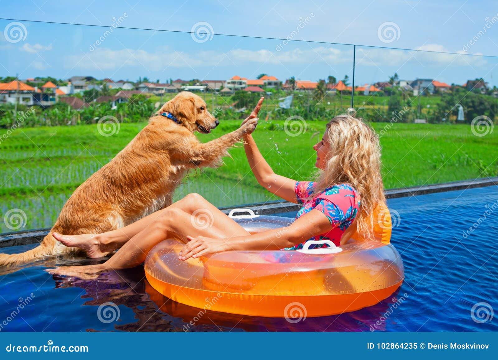 O cão dá a elevação cinco à natação feliz da menina na associação