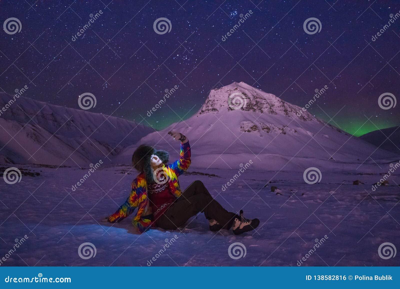 O céu ártico do aurora borealis da aurora boreal protagoniza na menina Svalbard do blogger do curso de Noruega na cidade de Longy