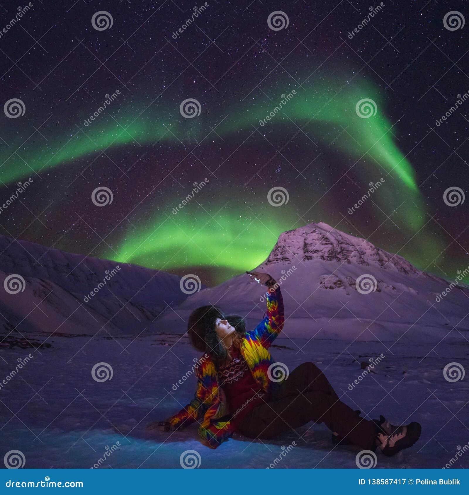O céu ártico do aurora borealis da aurora boreal protagoniza no homem Svalbard da menina do blogger do curso de Noruega na cidade