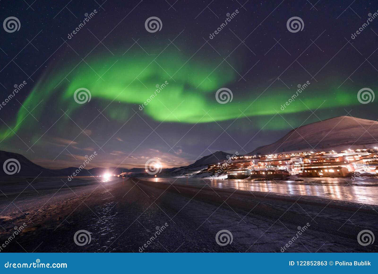 O céu ártico polar do aurora borealis da aurora boreal protagoniza em Noruega Svalbard em montanhas do curso da cidade de Longyea