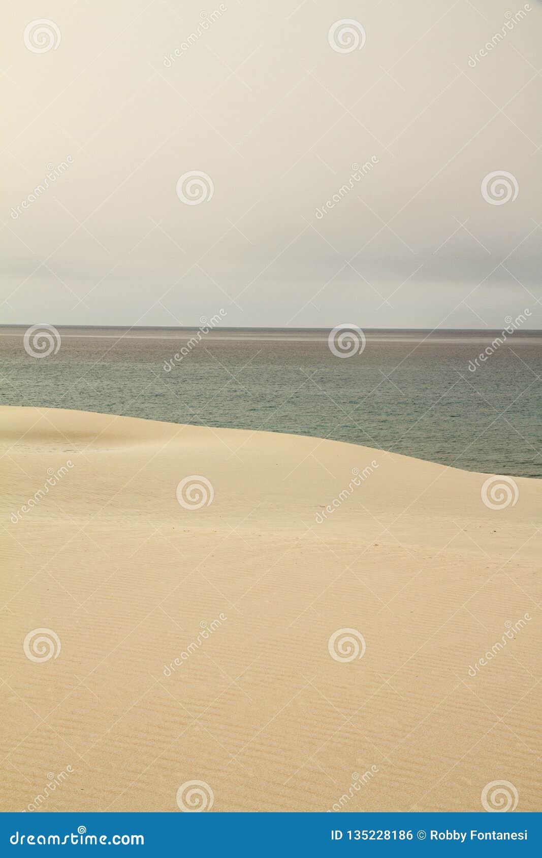 O céu cinzento quebra abruptamente no mar do inverno marcado harmoniosamente pela duna de areia amarela