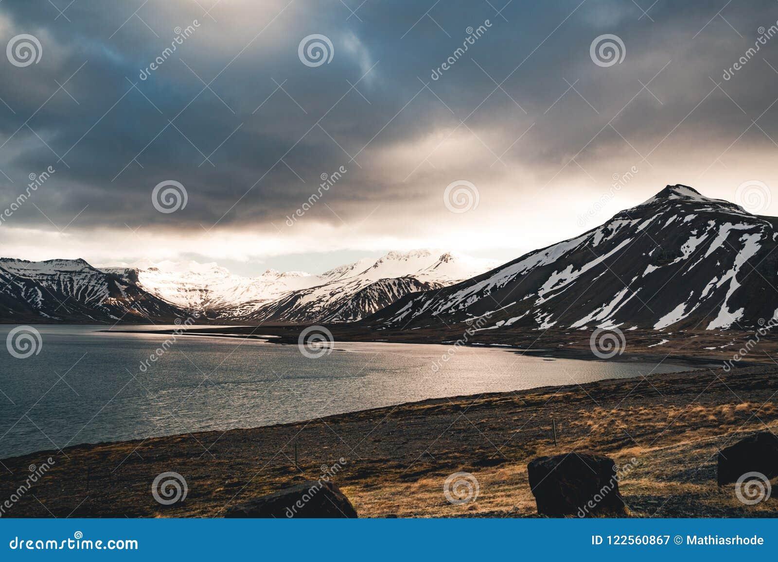 O céu dramático de Islândia com neve tampou a montanha na água do lago do oceano Lado do sul se o país