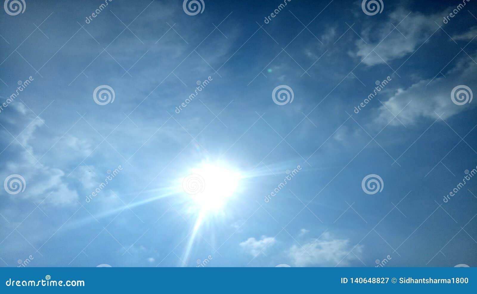 O céu Sun das nuvens irradia o dia ensolarado bonito afiado do brilho do sol dos raios brilhantemente com o papel de parede bonit