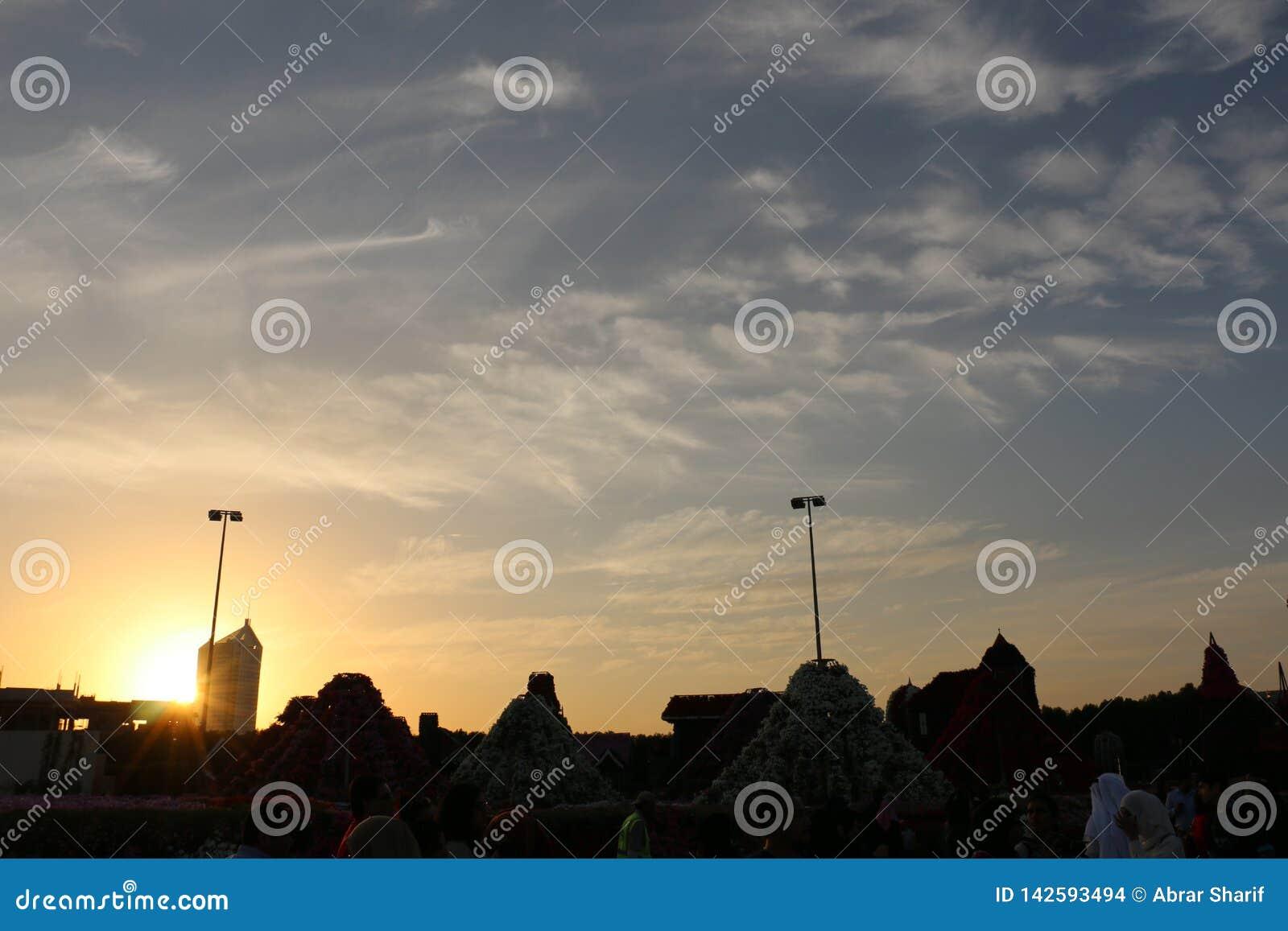 O c?u azul dram?tico do nascer do sol com sol alaranjado irradia a quebra atrav?s das nuvens Fundo da natureza Conceito da espera