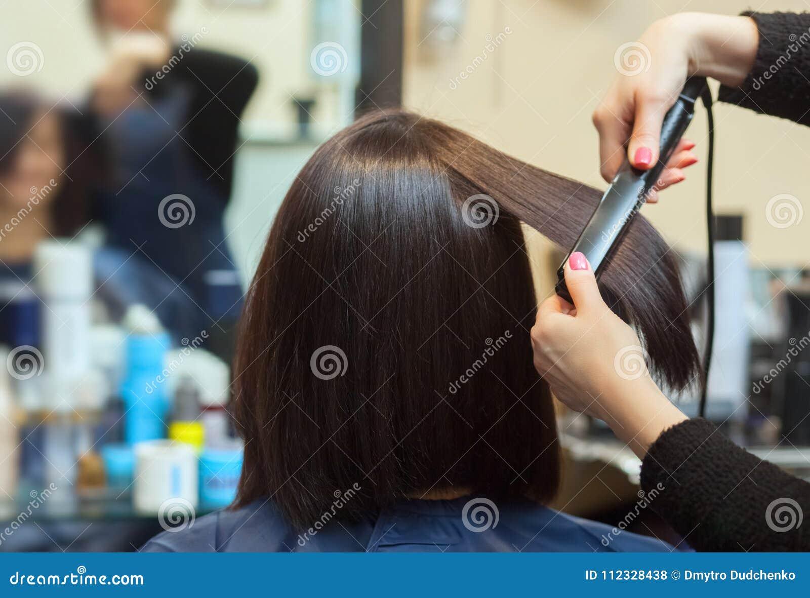 O cabeleireiro faz alinha o cabelo com o ferro a uma moça, morena do cabelo em um salão de beleza