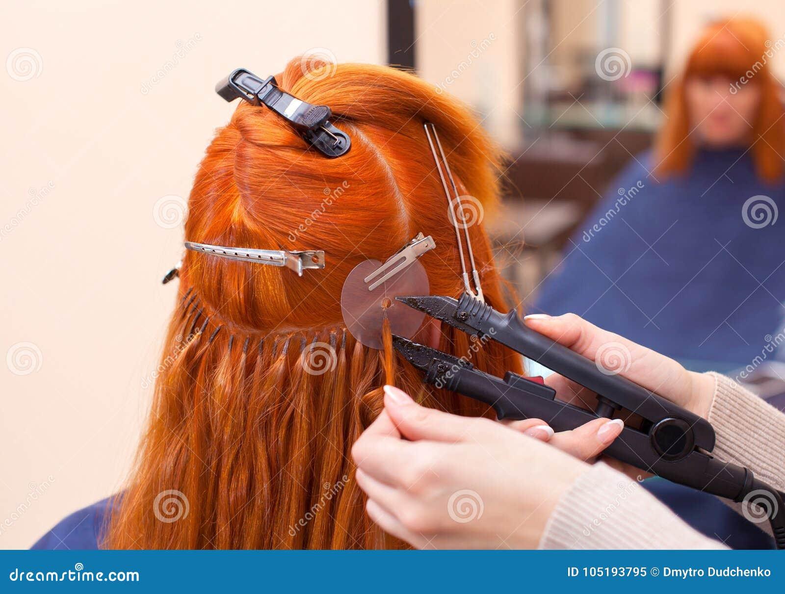 O cabeleireiro faz extensões do cabelo a uma menina nova, ruivo, em um salão de beleza