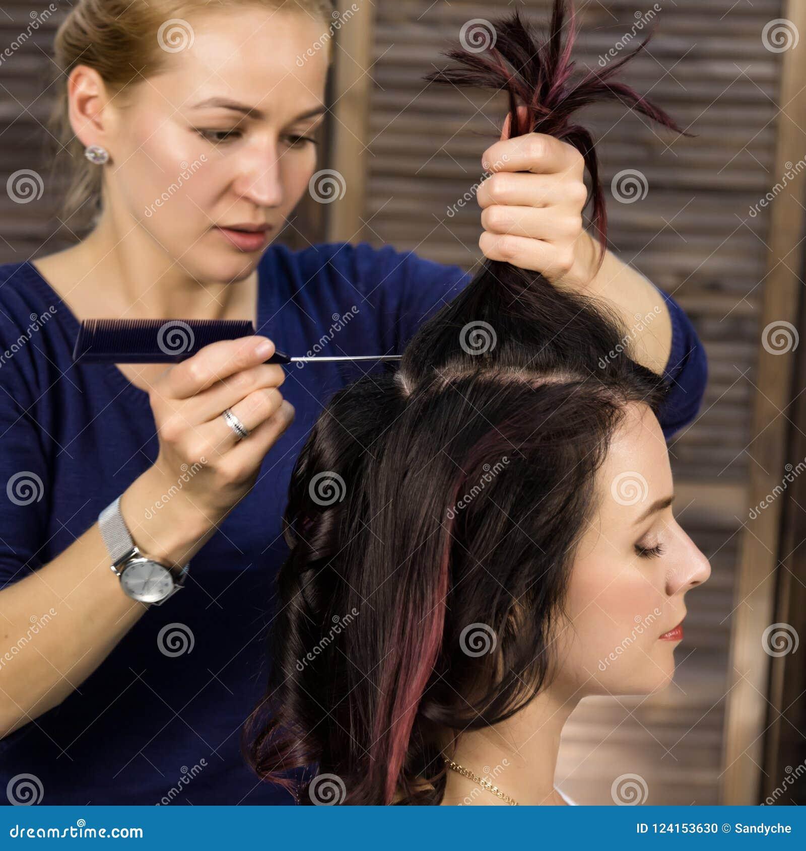 O cabeleireiro faz o penteado para a mulher luxuoso corte de cabelo sob a forma da onda grande Penteado do casamento do conceito