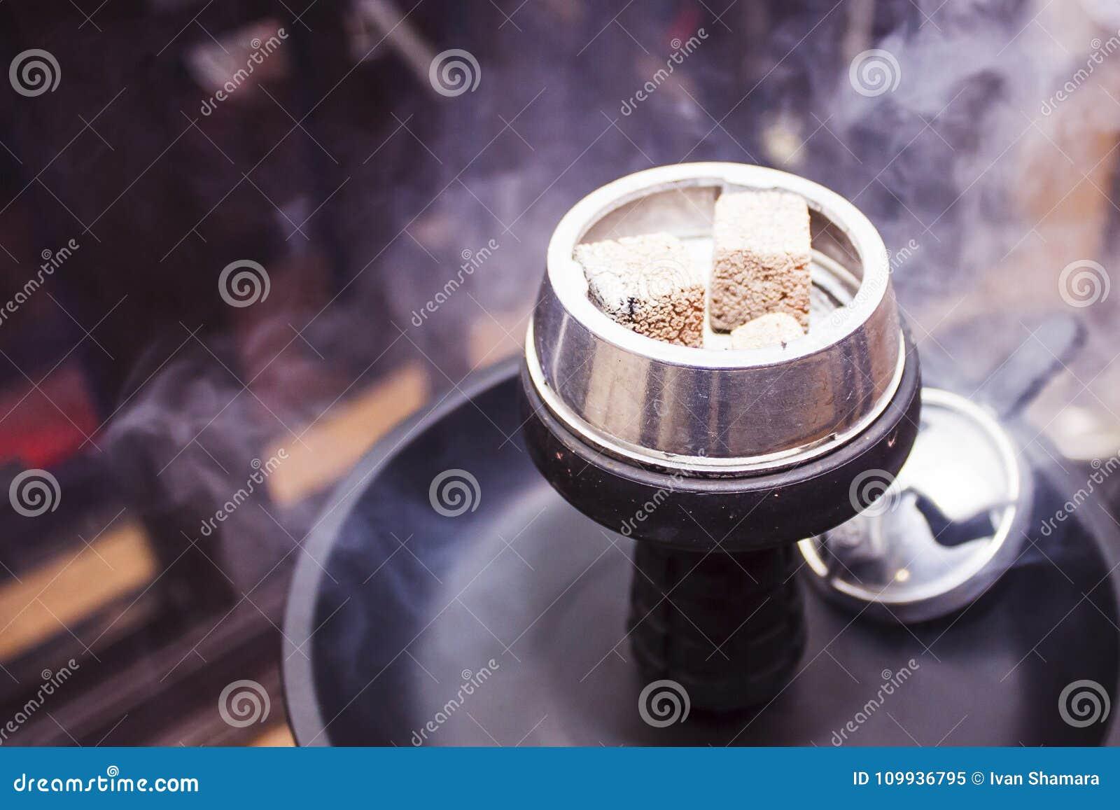 O cachimbo de água com carvões ardentes está na tabela