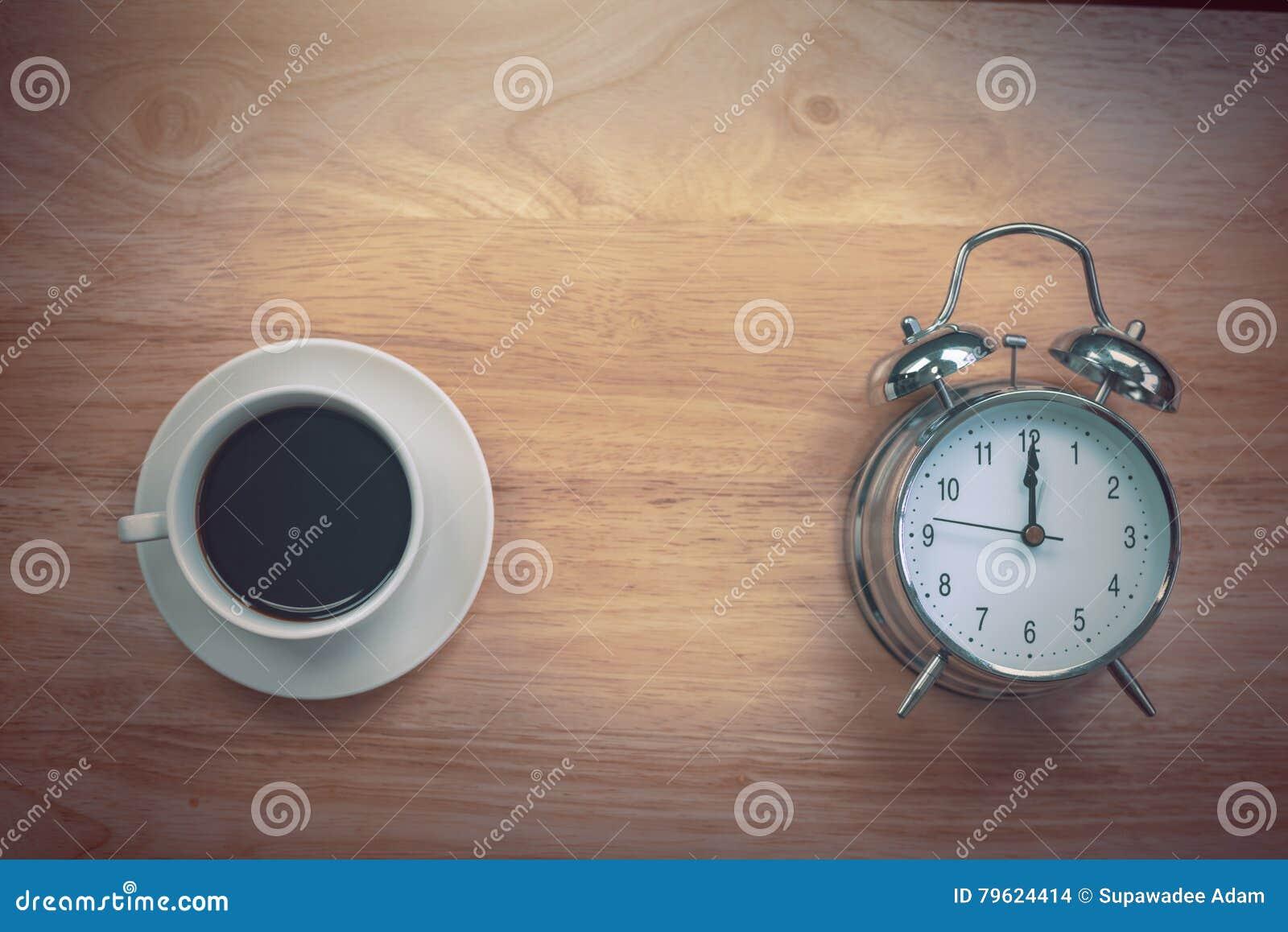 O caderno aberto do café preto com despertador antiquado corteja sobre