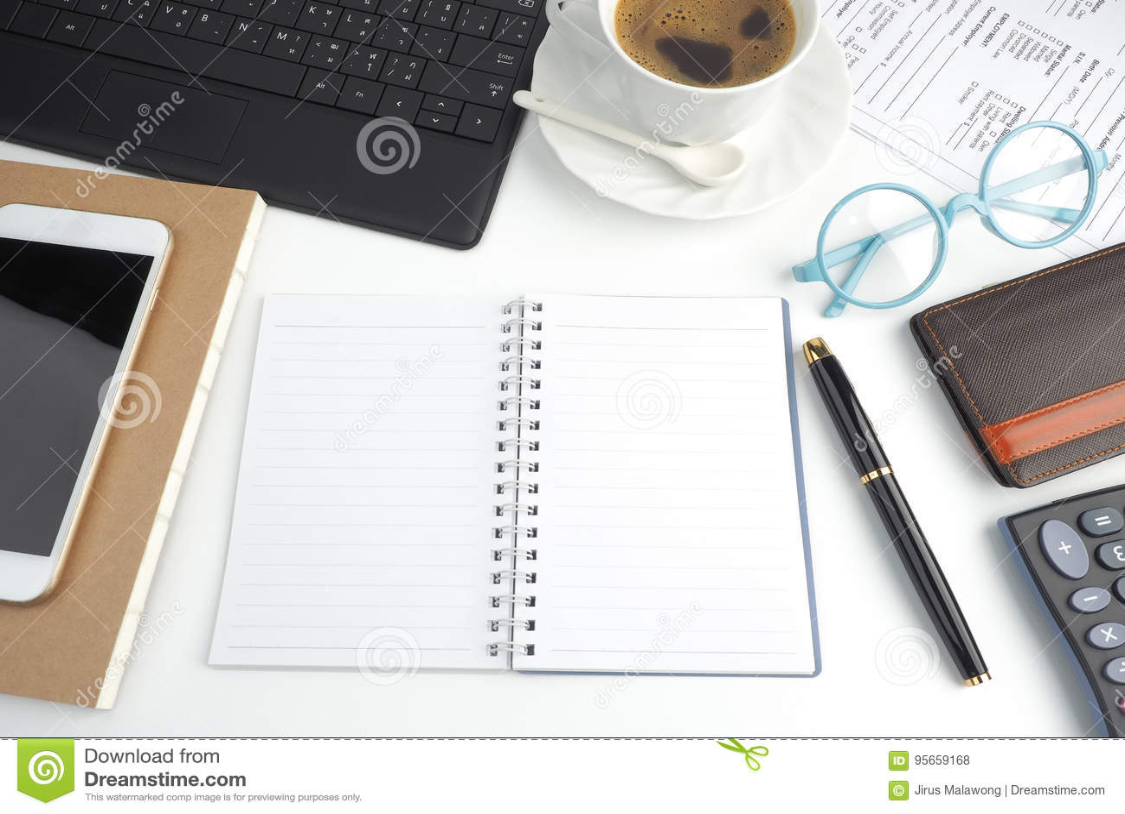 O caderno da página vazia no desktop branco com pena, café, lapto