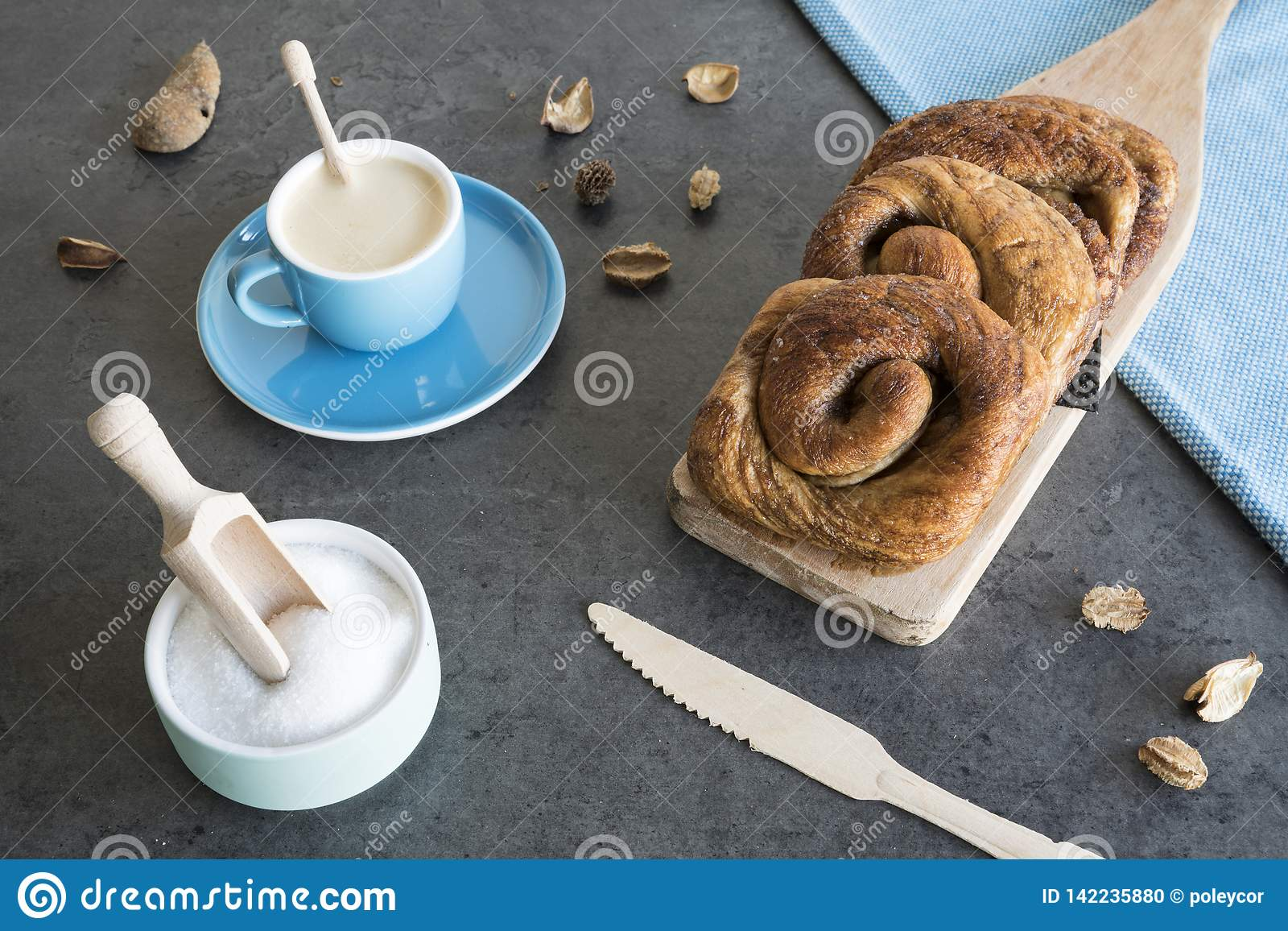 O café da manhã com rolo de pão holandês típico da canela chamou 'taças e xícara de café