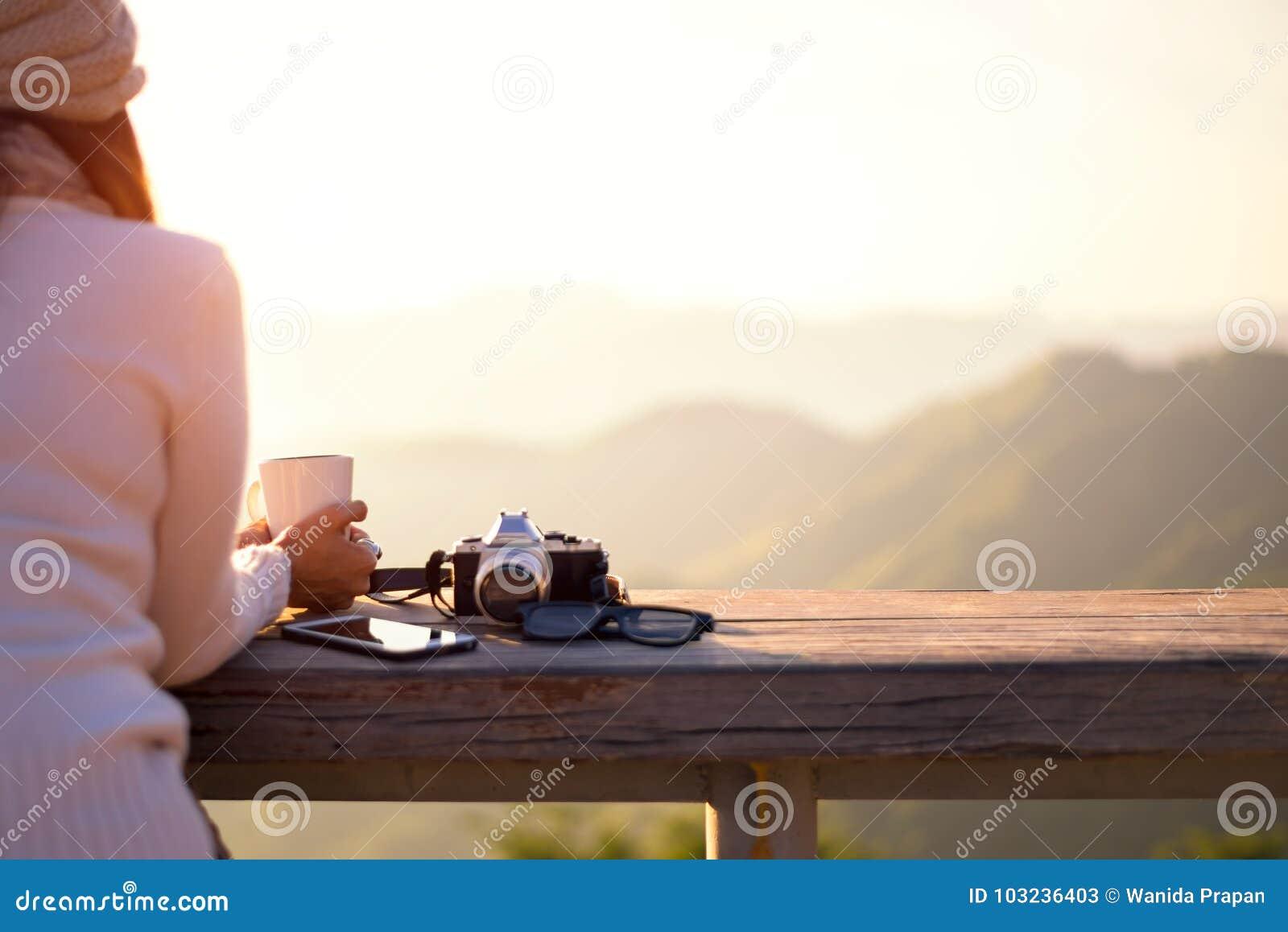 O café bebendo de sorriso e o chá da mulher asiática e tomam uma foto e relaxam no assento do sol exterior na luz do sol clara ap