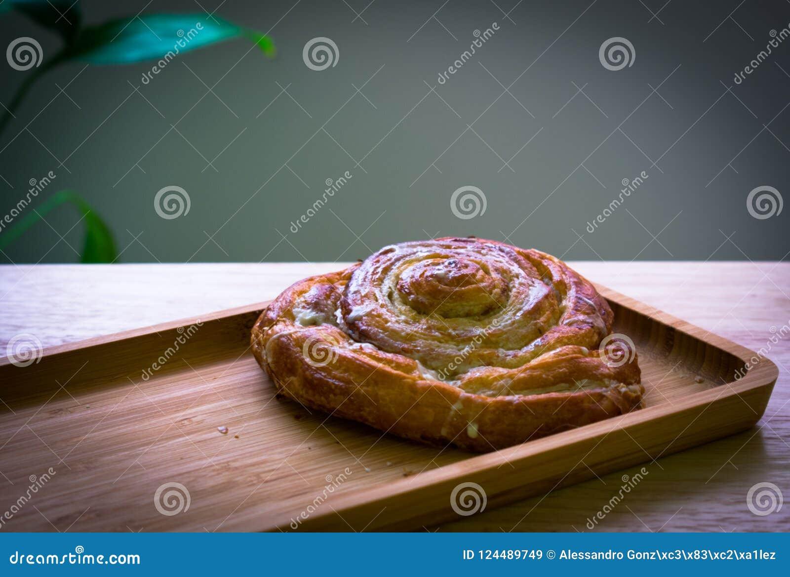 O café da manhã cozeu o rolo, almods com backgroud de madeira