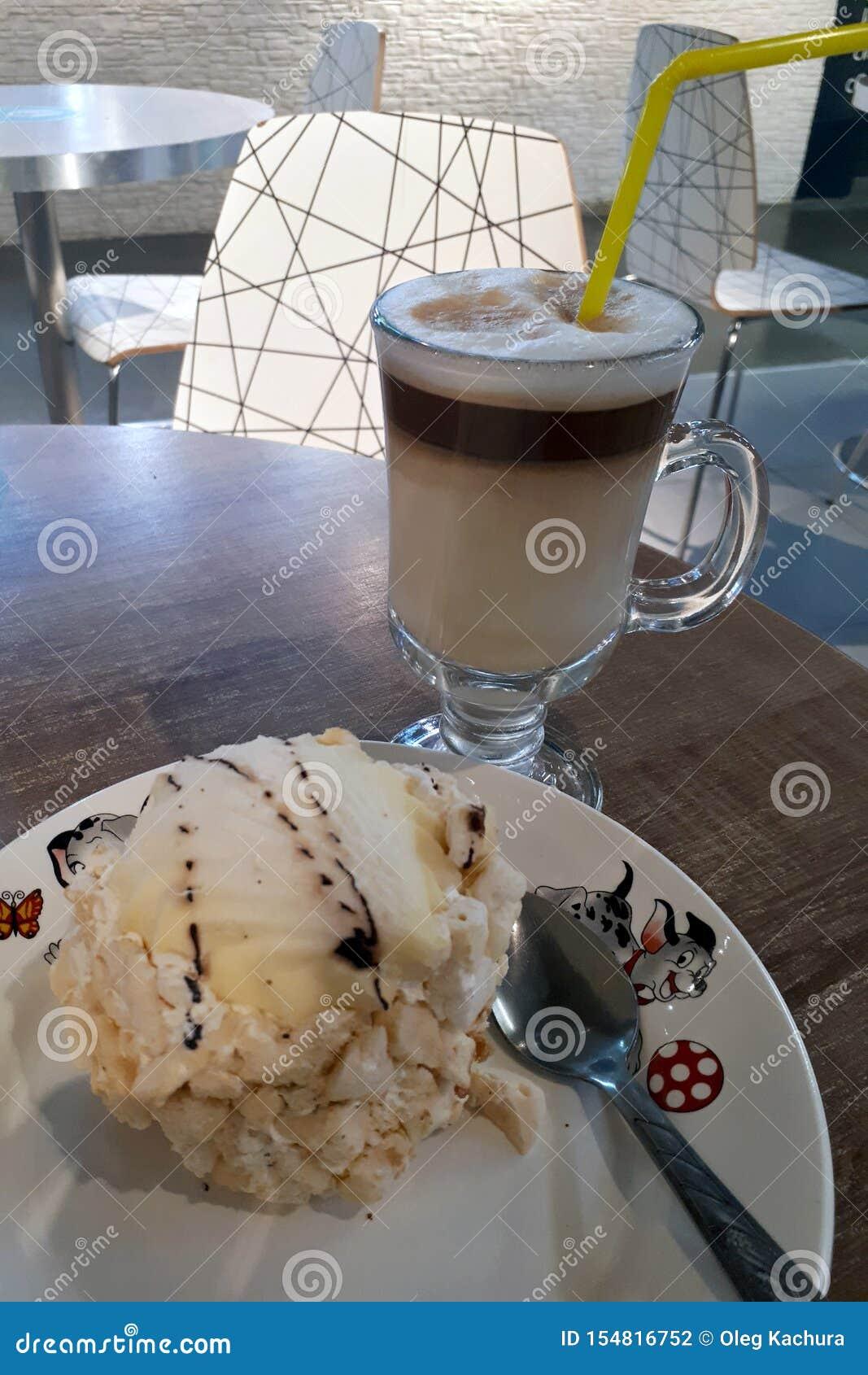 O café do cappuccino está em uma tabela com bolo em uma placa