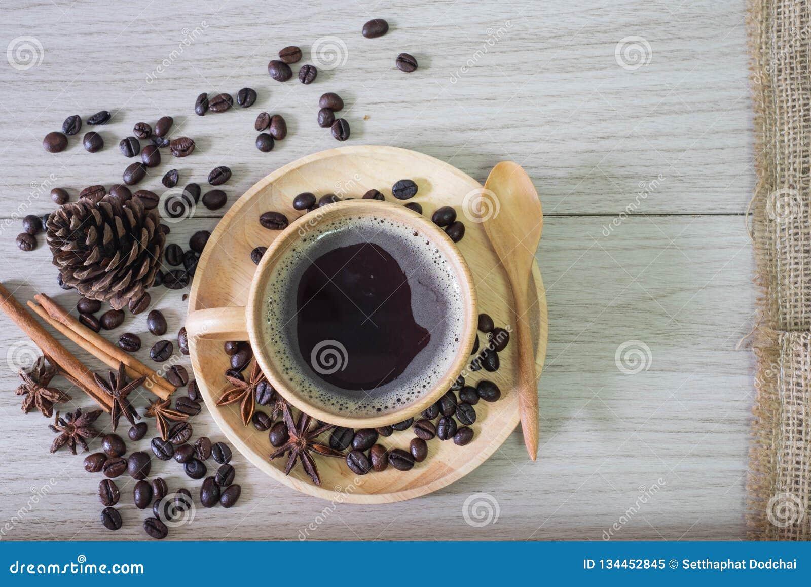 O café preto em feijões de madeira do copo e de café derrama no fundo de madeira