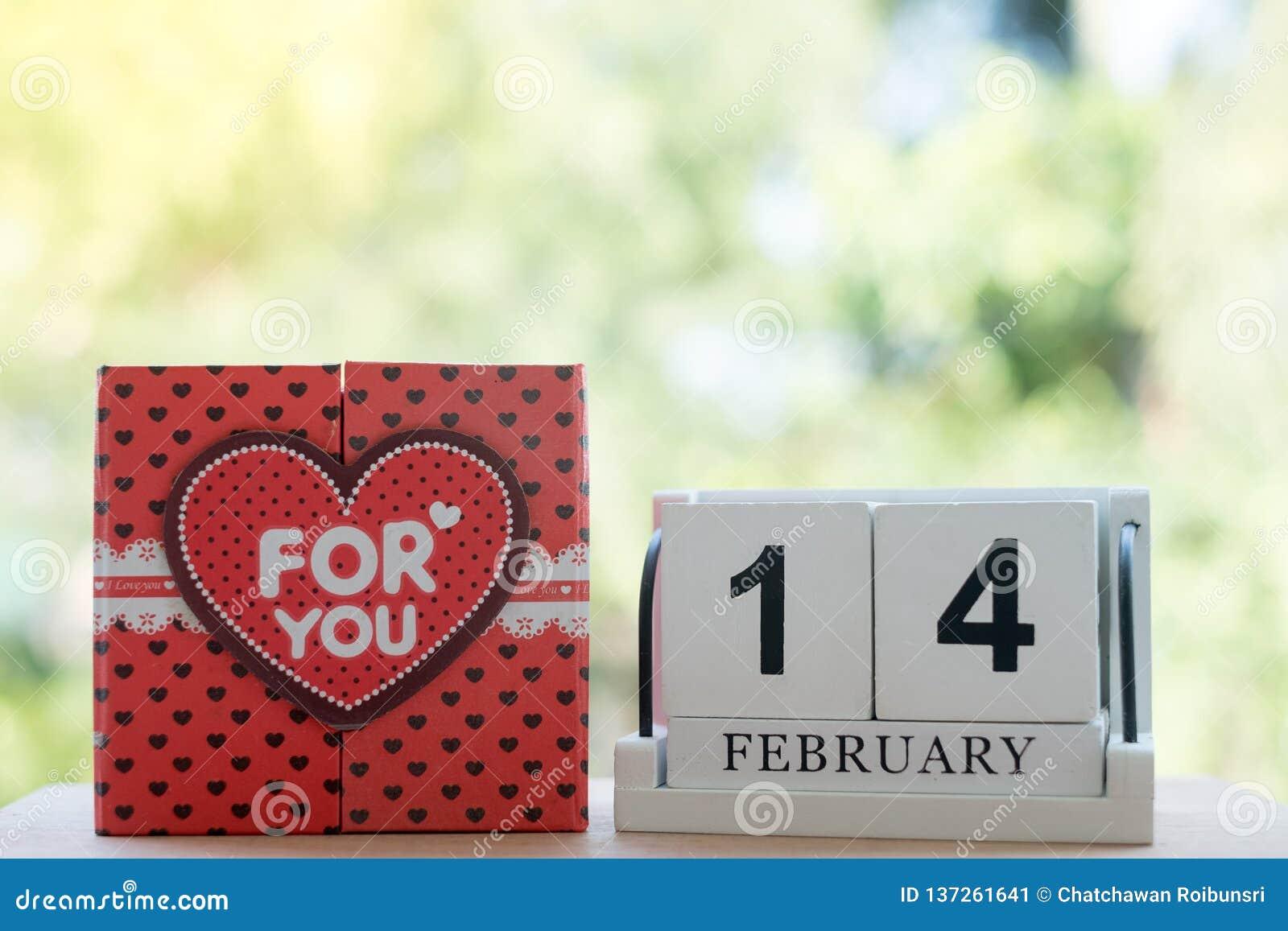 O calendário de madeira, o 14 de fevereiro, consiste em uma caixa dos corações vermelhos que são escritos para você, colocada de