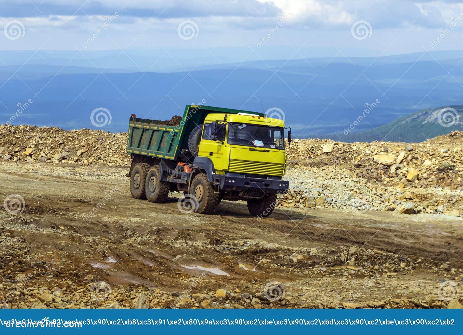 O caminhão basculante está conduzindo em uma estrada da montanha