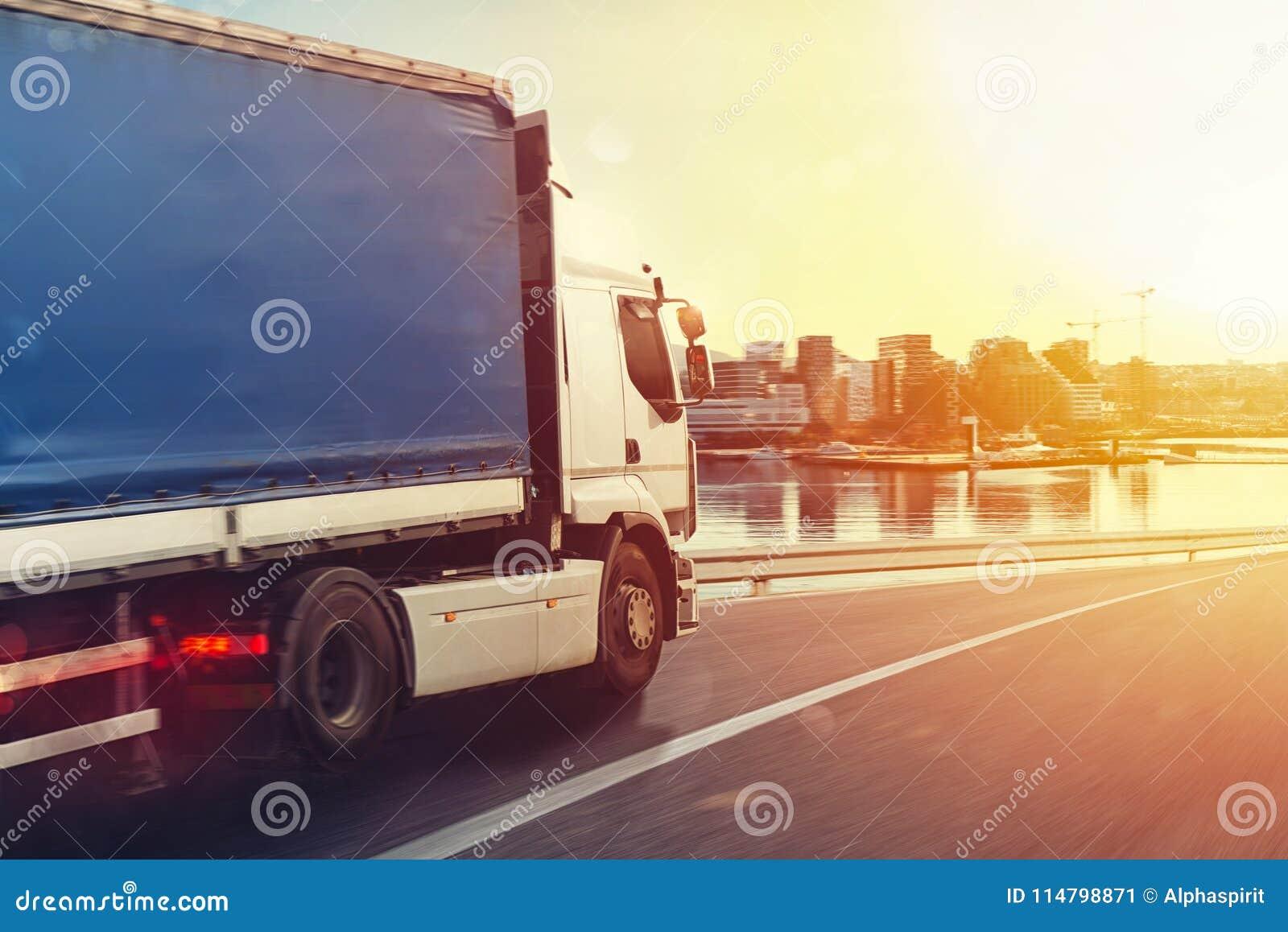 O caminhão corre rapidamente na estrada para entregar