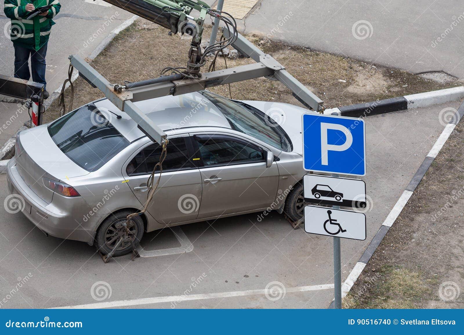 O caminhão de reboque carrega o carro para a violação das regras do estacionamento reparo