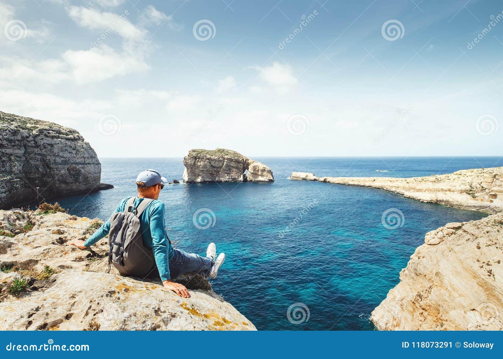 O caminhante litoral relaxa no beira-mar rochoso