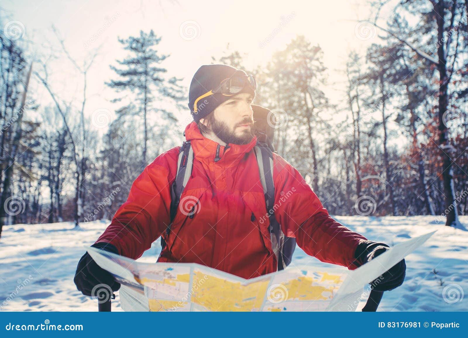 O caminhante perdido verifica o mapa na floresta nevado