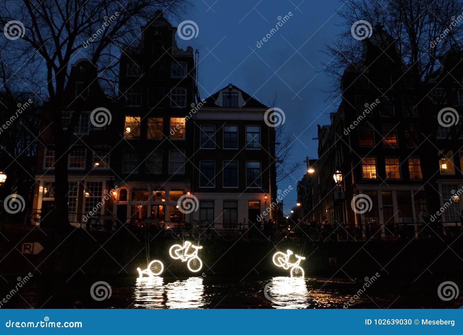 """O canal iluminado Bikes """"15000 e  do more†na noite no festival da luz de Amsterdão"""