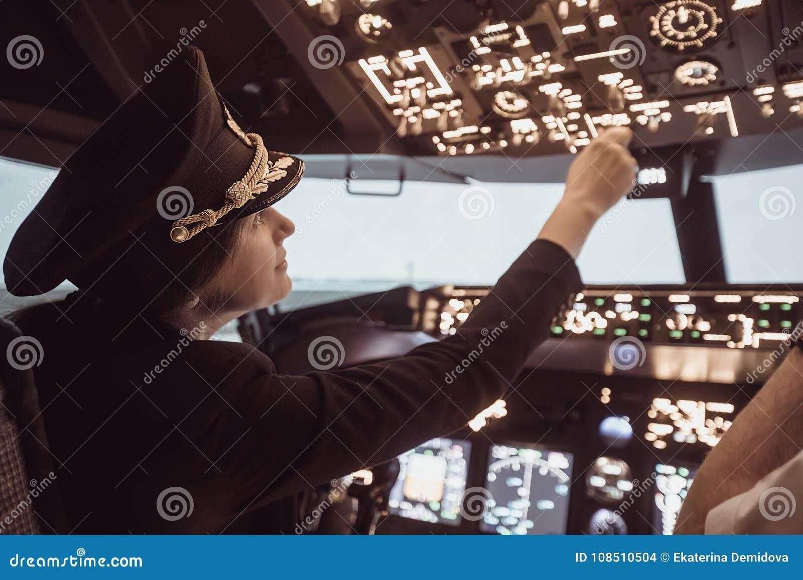 O capitão piloto fêmea prepara-se para o plano da decolagem