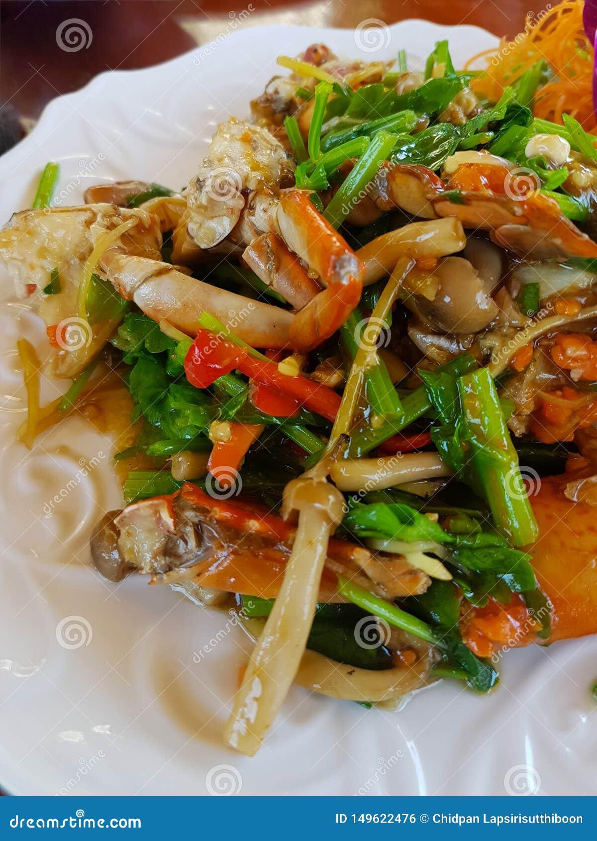 O caranguejo fritado com pó de caril em um prato branco colocou