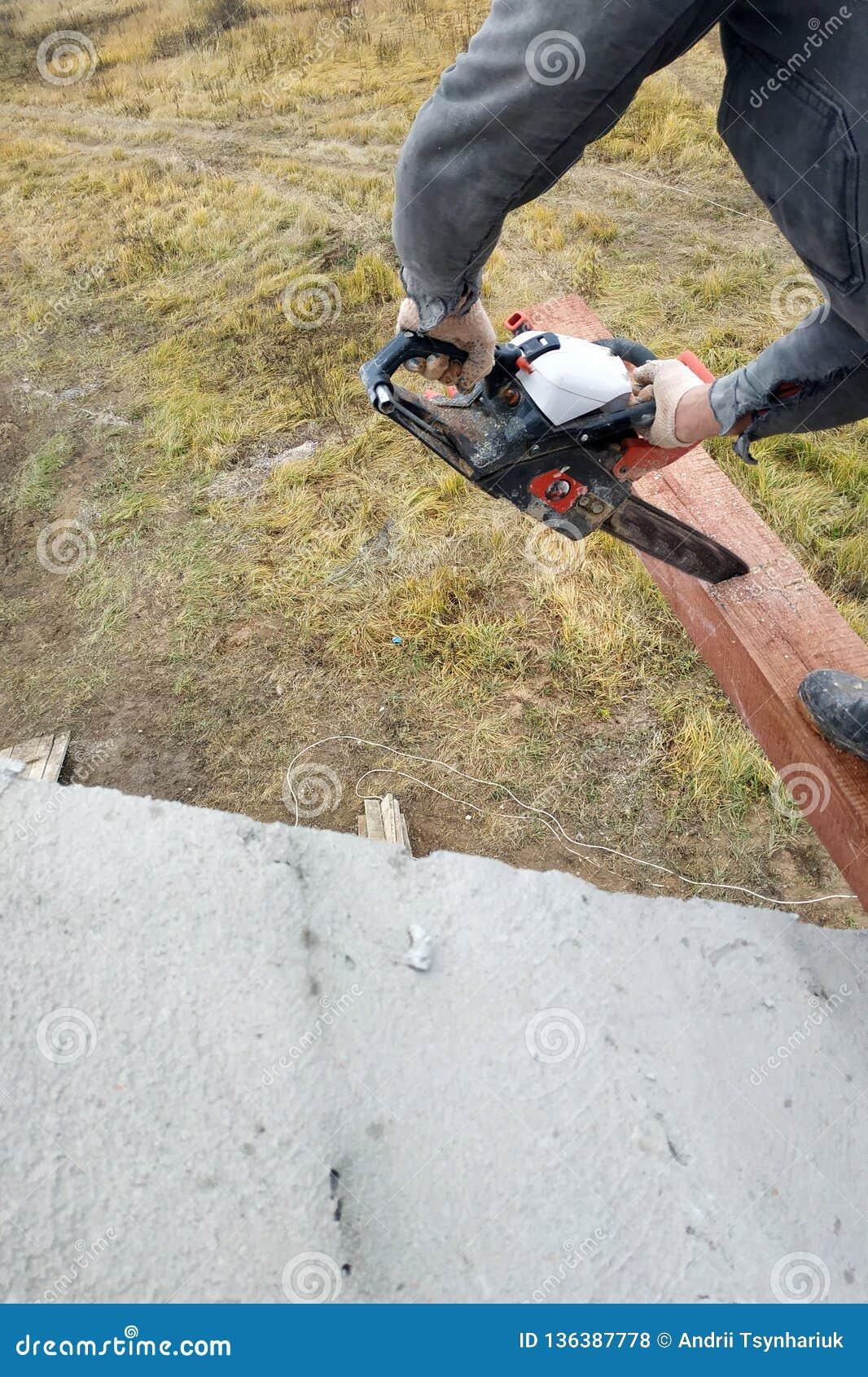 O carpinteiro com uma serra de cadeia faz bebeu em uma construção do feixe de madeira das casas