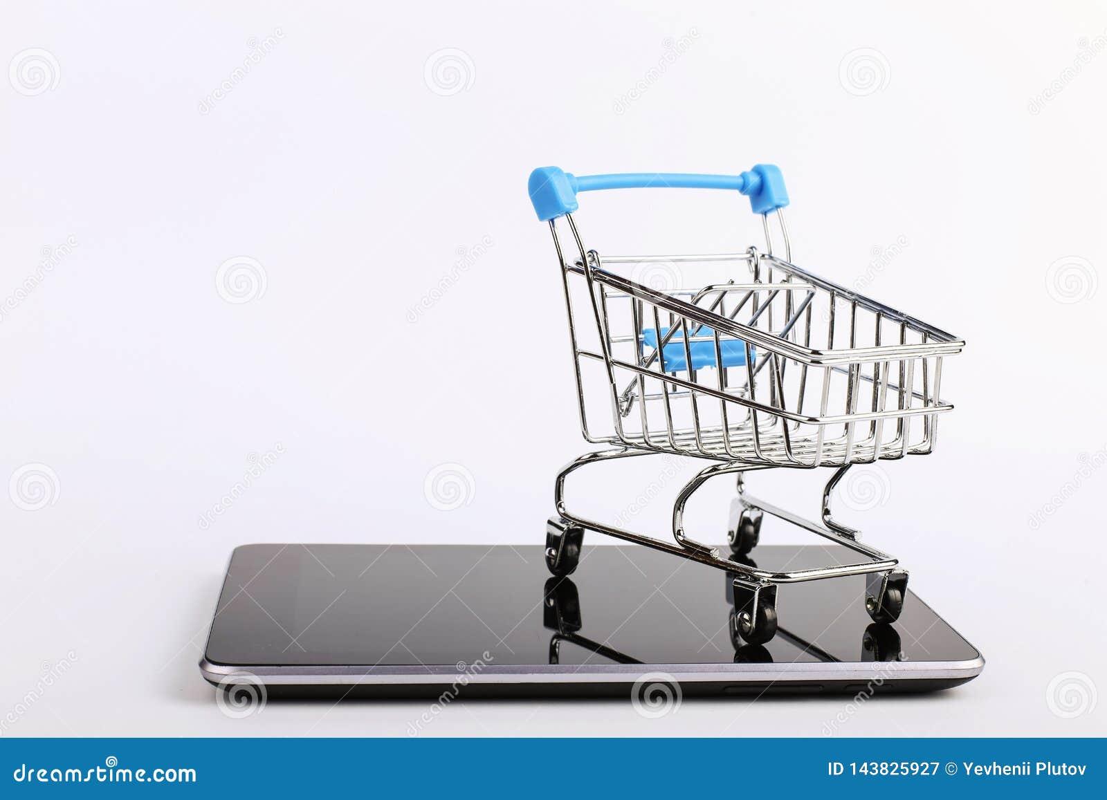 O carrinho de compras est? no smartphone Conceito em linha das vendas