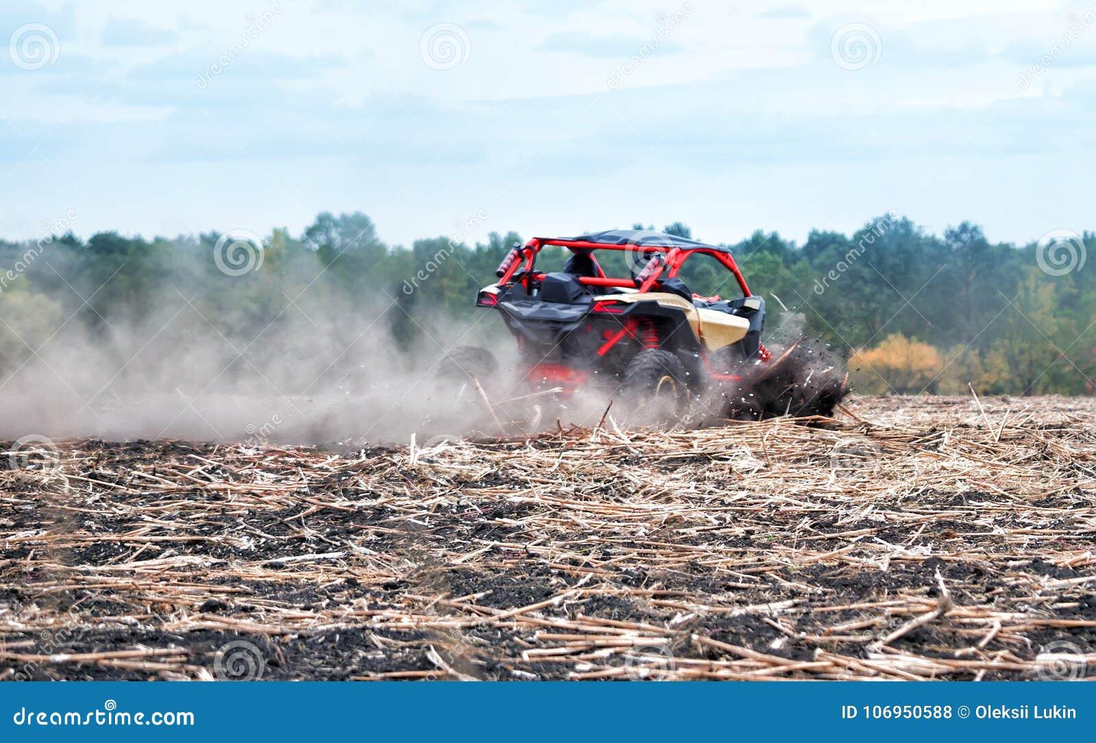 O carrinho vermelho apressa-se através do campo na poeira