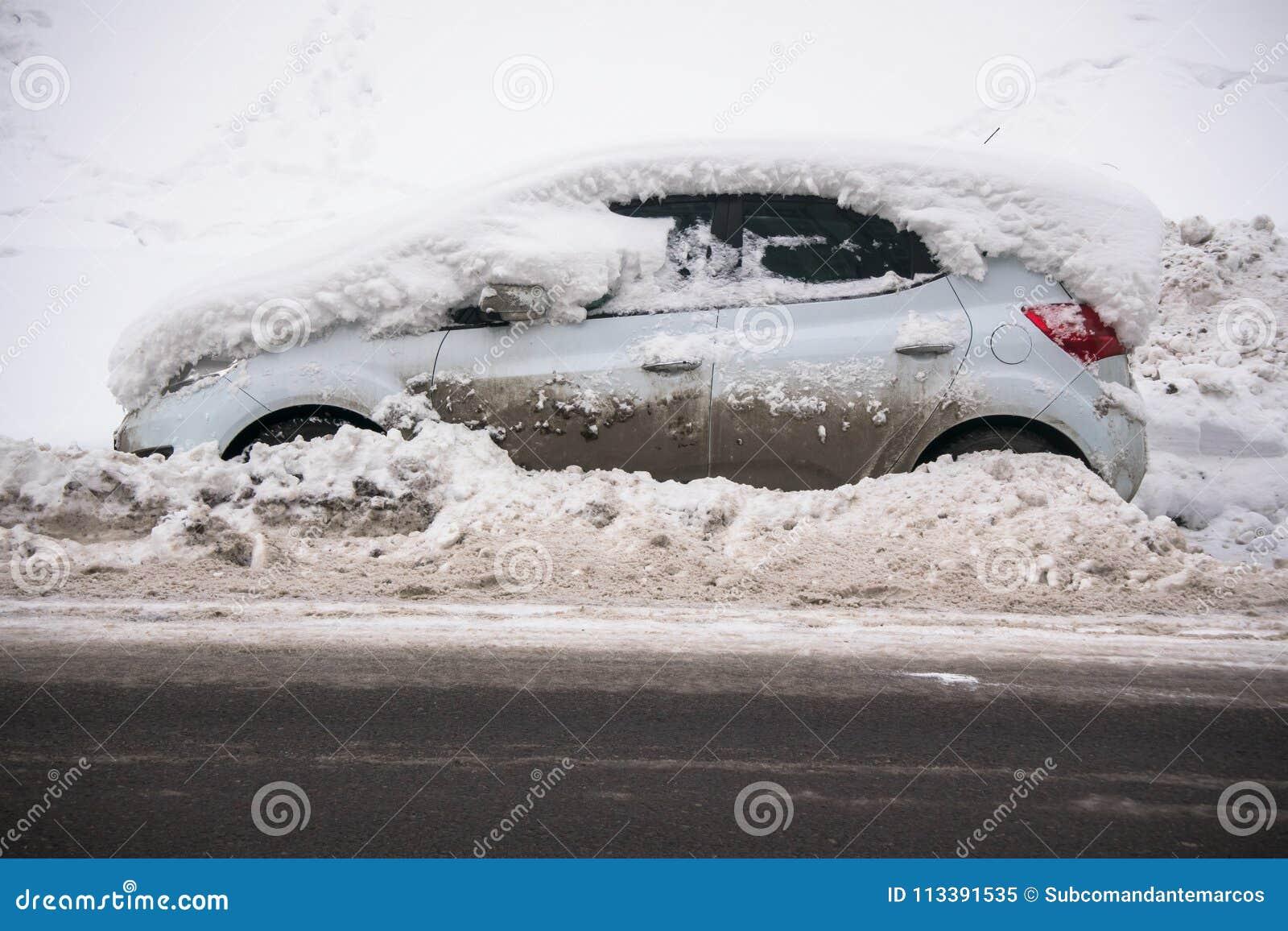 O carro, coberto com a camada grossa de neve e de lama, na estrada