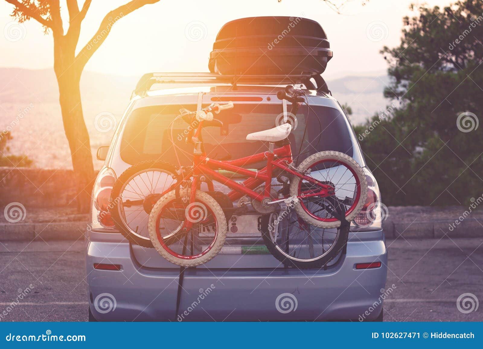 O carro de família com a cremalheira de bicicletas pequena das crianças, apronta-se para o curso, fazendo uma ruptura no estacion