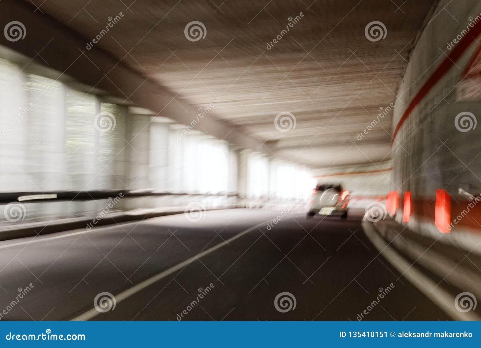 O carro está movendo-se rapidamente através do túnel borrado unsharply