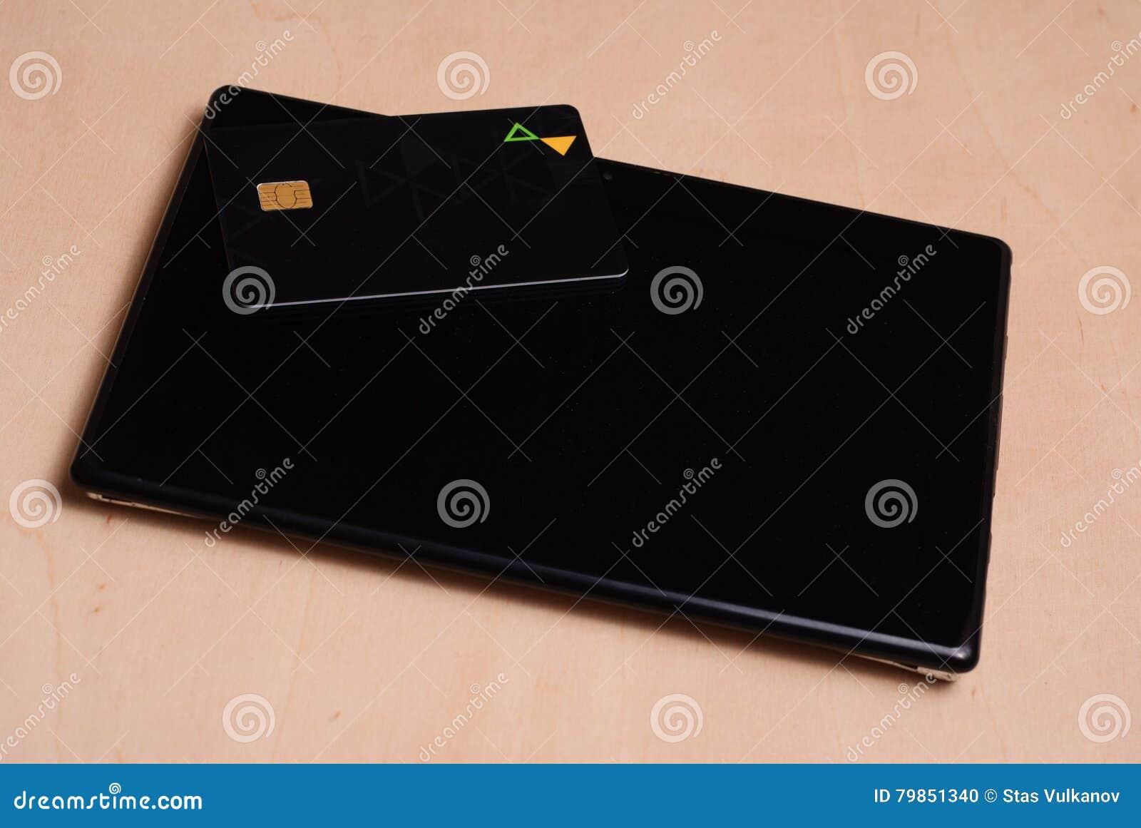 O cartão de crédito preto está em uma tabuleta eletrônica preta,