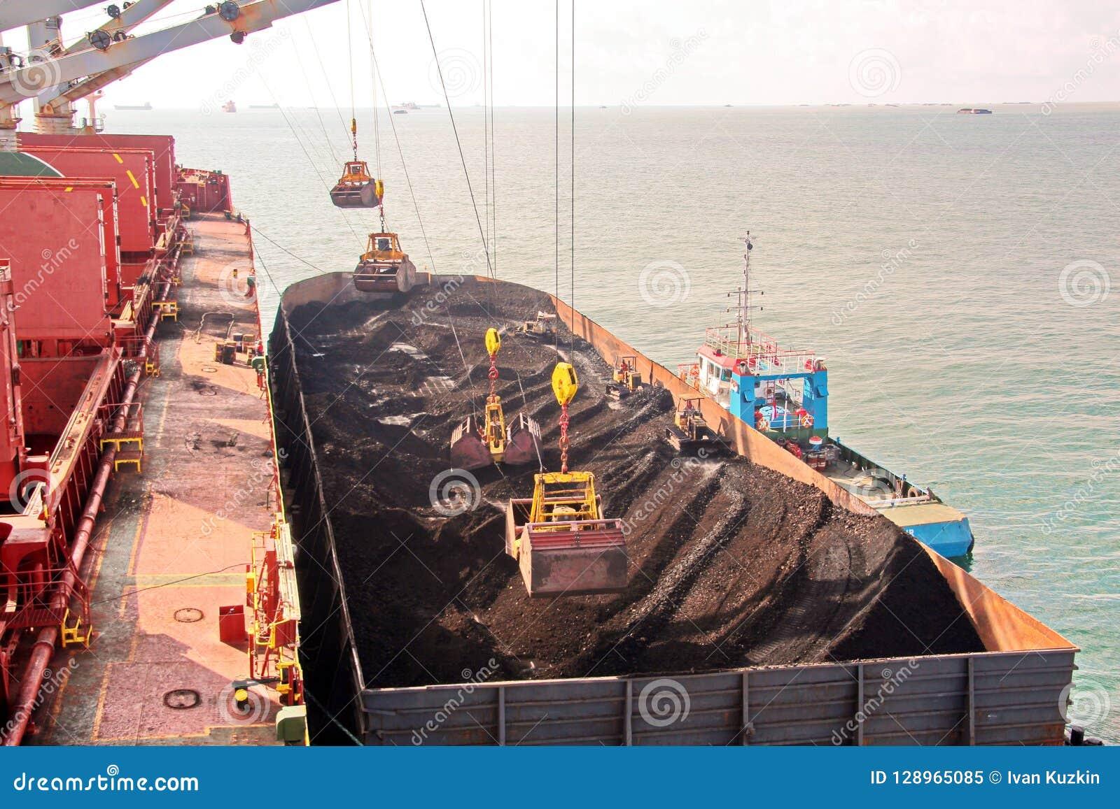 O carvão da carga das barcas da carga em um portador de maioria que usa o navio cranes e garras no porto de Samarinda, Indonésia