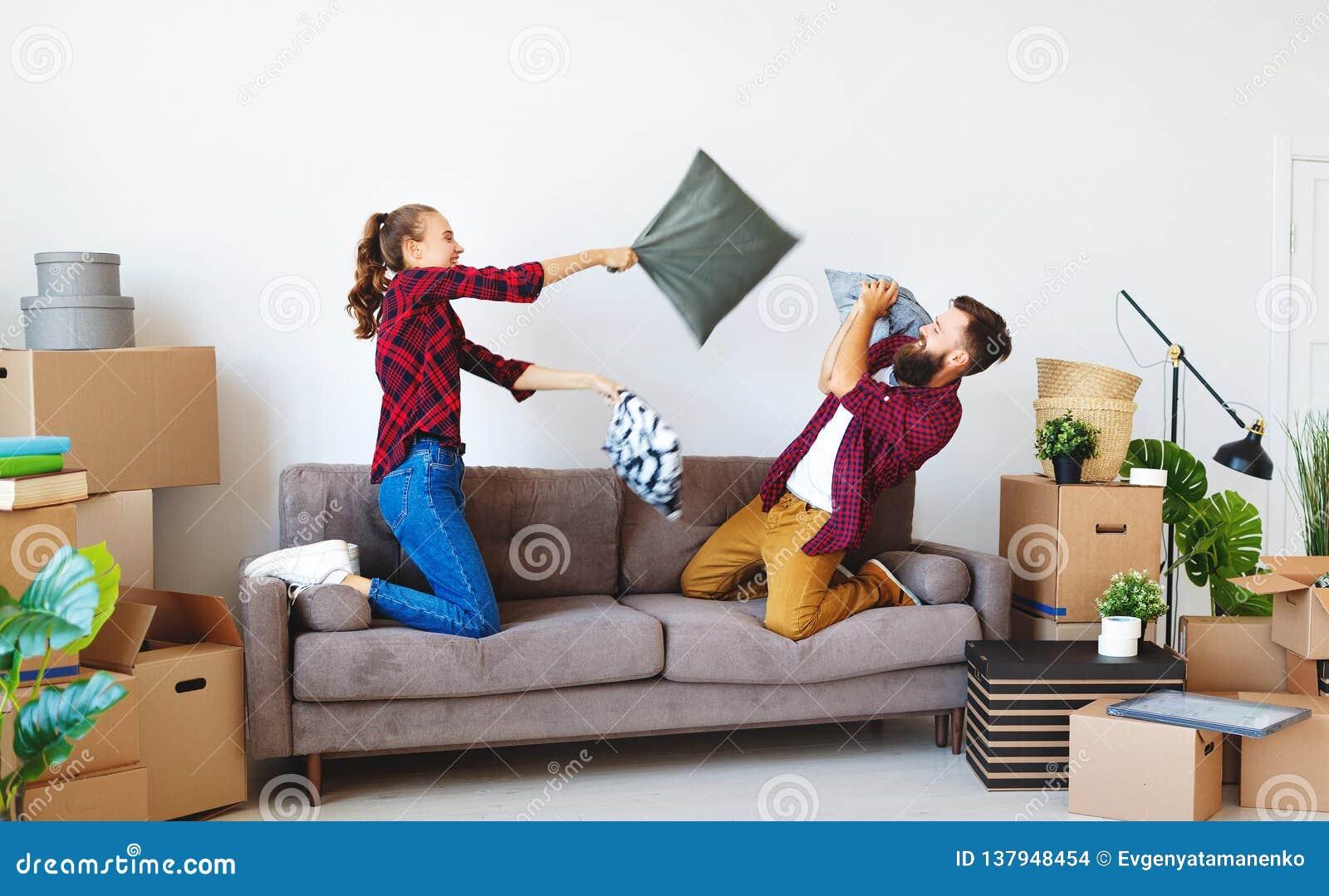 O casal novo feliz transporta-se ao apartamento novo e rindo, o salto, luta descansa