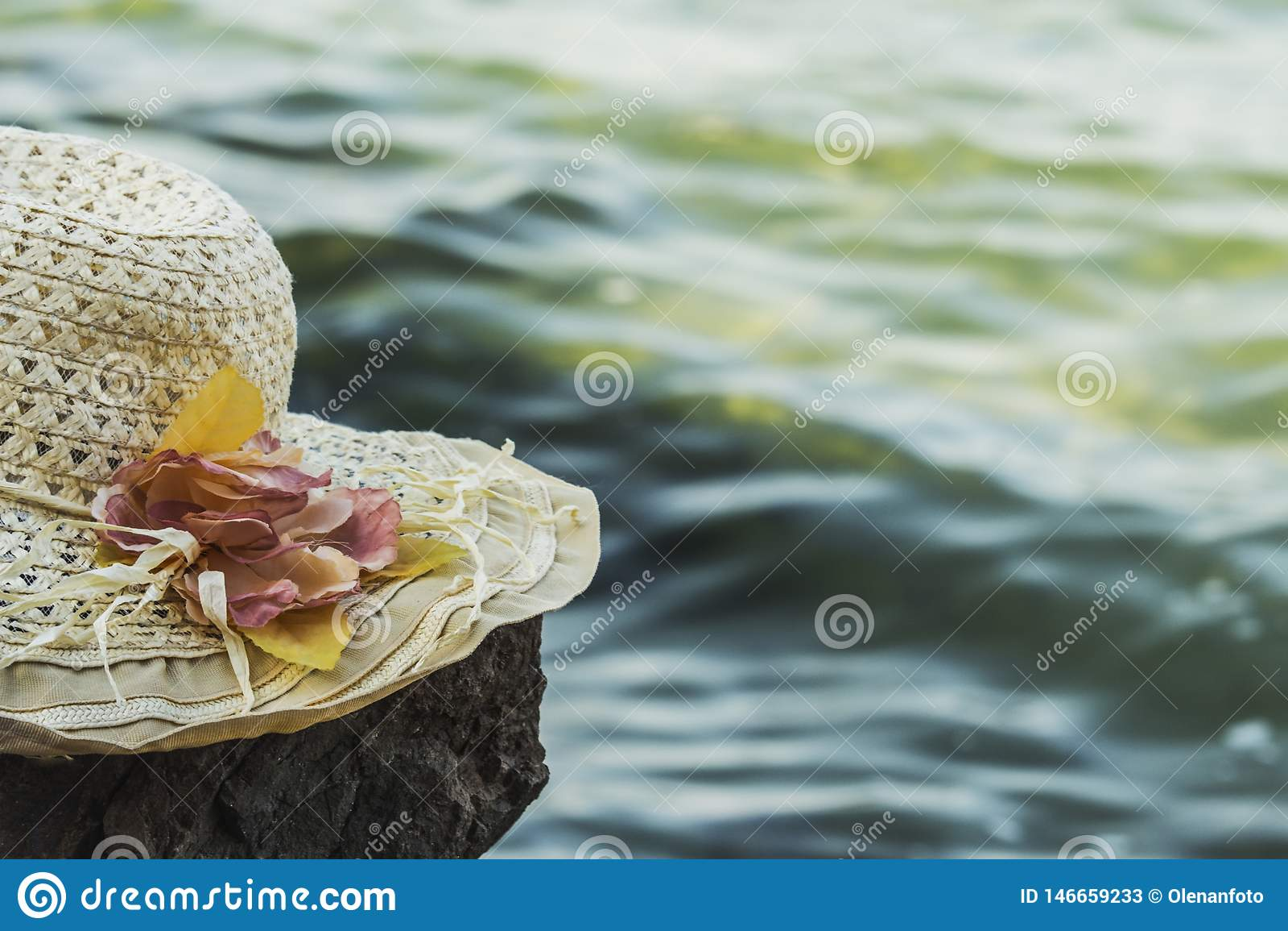 O chapéu ensolarado com flores encontra-se em uma rocha na frente do mar, tonificado