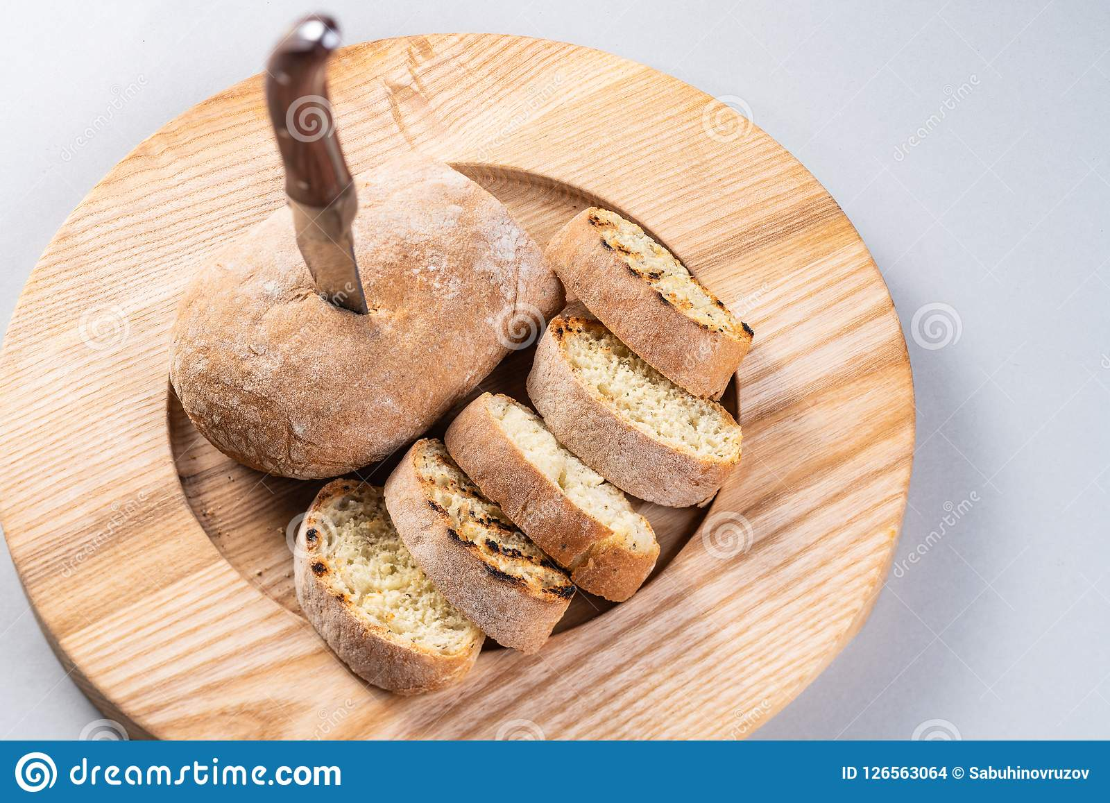 O ciabatta italiano cortou nas fatias em uma placa de madeira Pão caseiro com uma faca