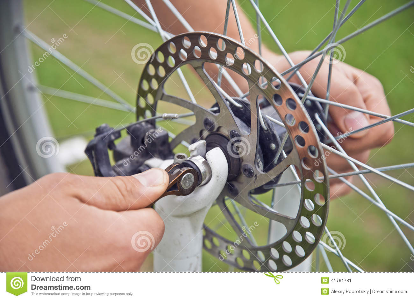 O ciclista do homem verifica a roda de freio da bicicleta