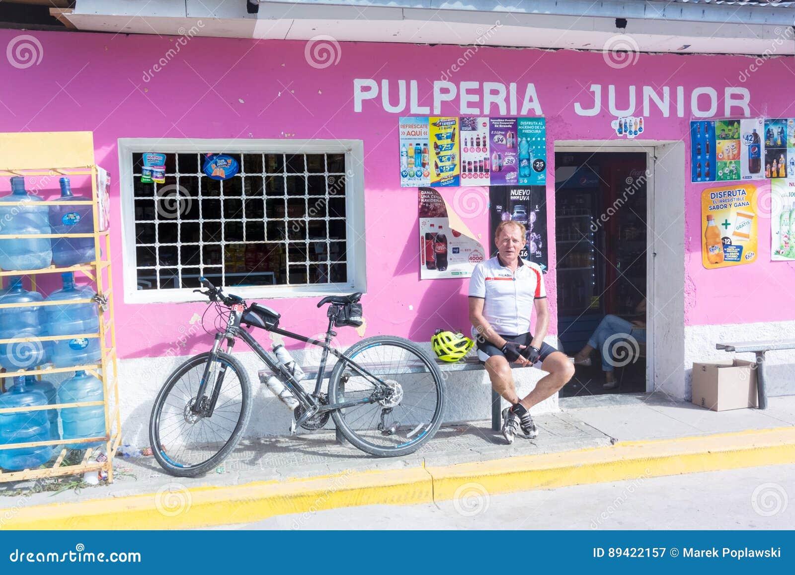 O ciclista, está sentando-se no banco na frente da loja de canto no sma