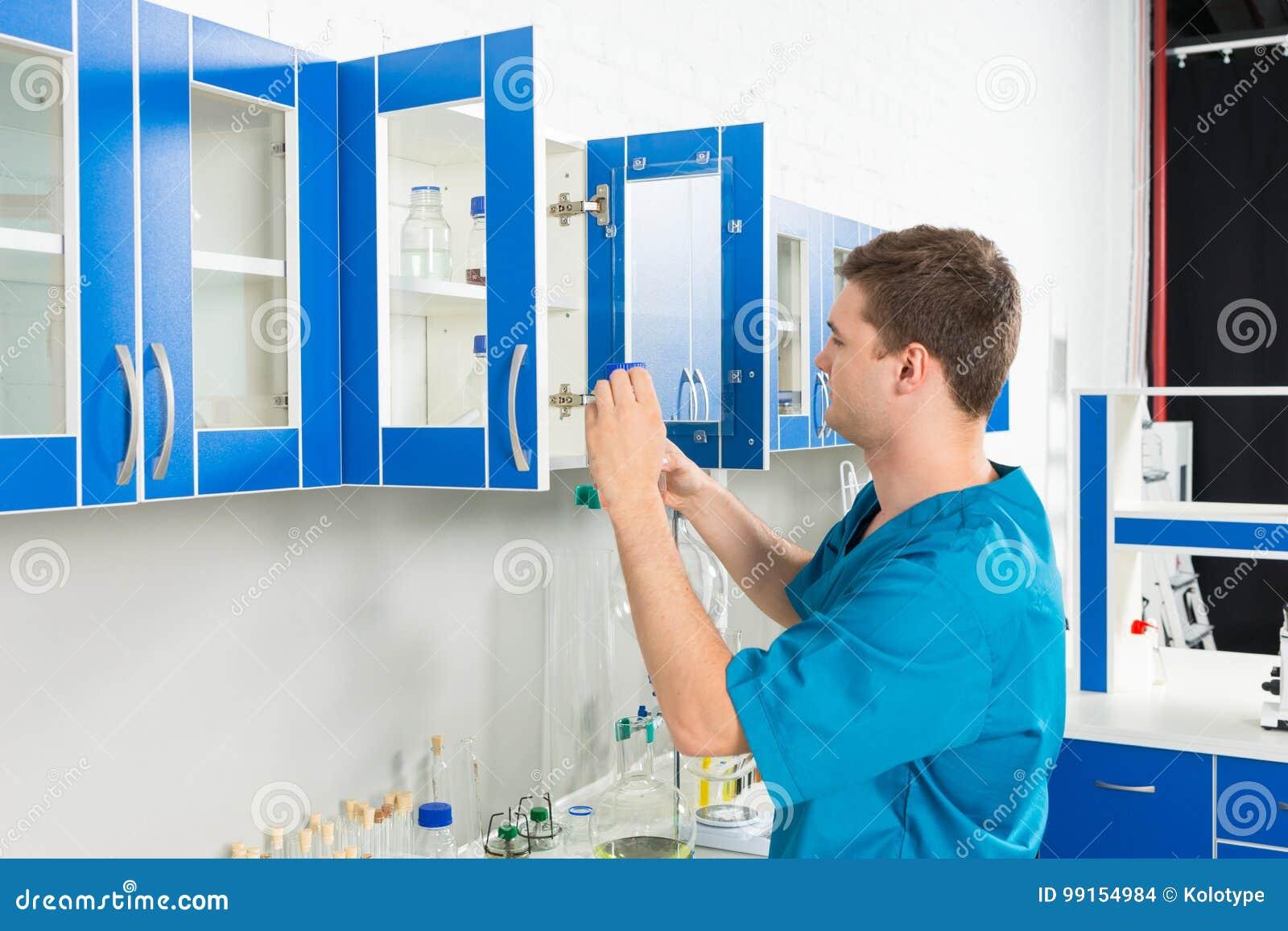 O cientista novo no uniforme está procurando algo no casos
