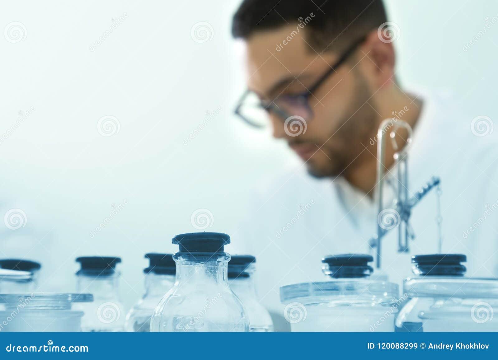 O cientista novo trabalha em um laboratório químico Foco selecionado