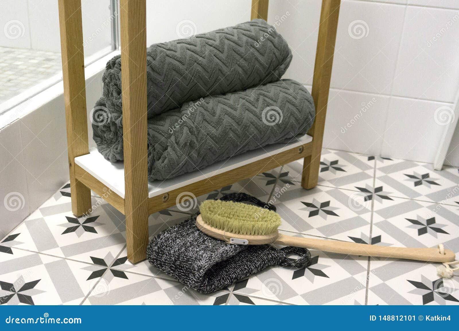 O cinza dobrou belamente toalhas em uma prateleira branca com uma escova e uma toalha de rosto da massagem